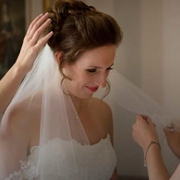 Hair dresser making the finishing touches to the hair of a bride wearing a white wedding dress and veil.