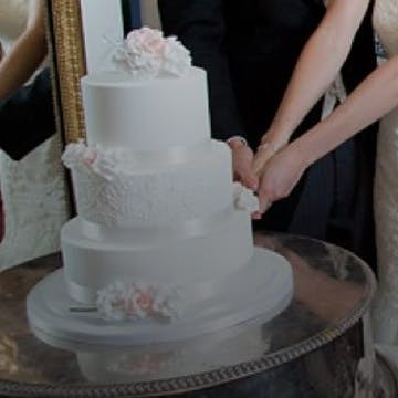 Couple cutting into a beautiful white three-layered wedding cake decorated with pink flowers.