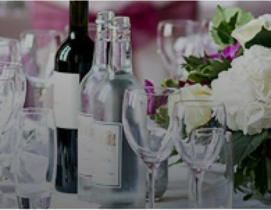 Gorgeous wedding table decorated with wine bottles, crystal glasses and wedding flowers.