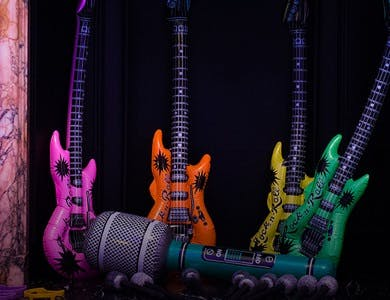 Three inflatable guitars in different colours and an inflatable microphone at a wedding for wedding entertainment.