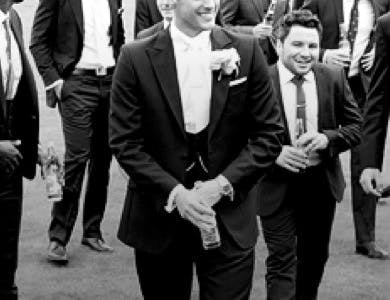 Groom wearing a black tuxedo and white flower boutonniere surrounded by his ushers.