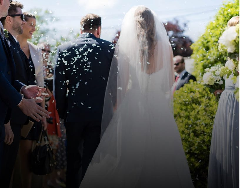 Artistic wedding photo of a newlywed couple leaving church whilst their friends throw confetti.