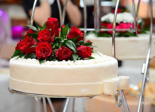 Wedding cake with white icing and a bouquet of red roses on top, in a wedding bakery