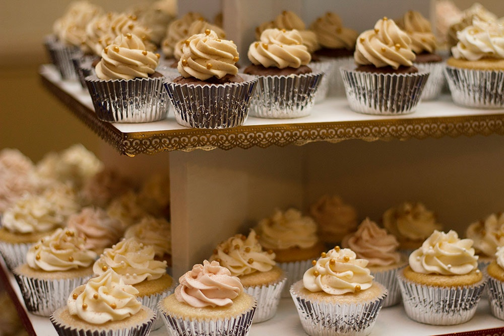 Two shelves filled with gold and cream decorated wedding cupcakes in silver muffin liners