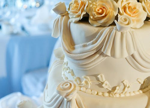 Three-level wedding cake deocrated with white icing and a bouquet of edible white roses on top