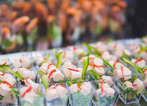 Small transparent cups filled with mini salads, aligned on a table for a buffet reception