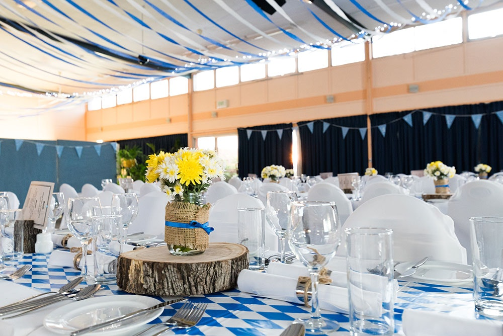 Conference hall dressed for a dinner reception, decorated with blue and white bunting and fairy lights