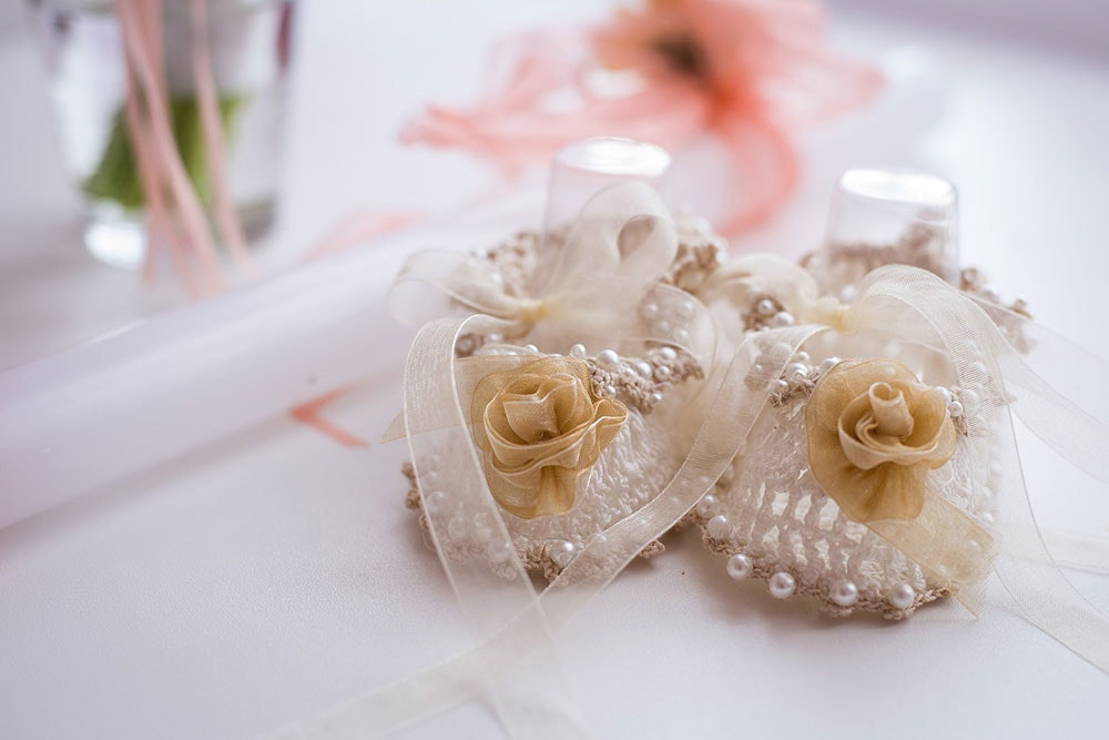 White wedding earrings made of ribbon, pearls, crochet and a cream fabric flower, resting on a dressing table