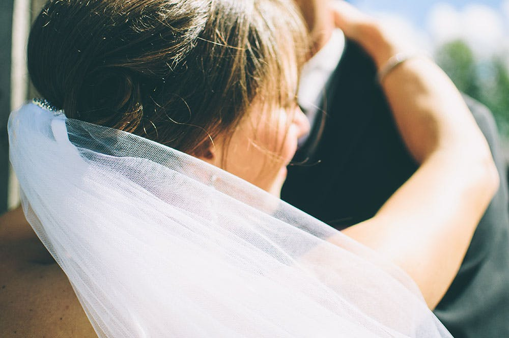 A bride embracing her groom with her white wedding hair veil floating in the wind