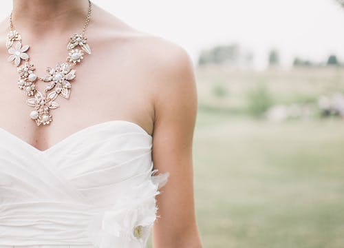 Bride's bustier wedding dress with golden flower necklace and a field as the backdrop
