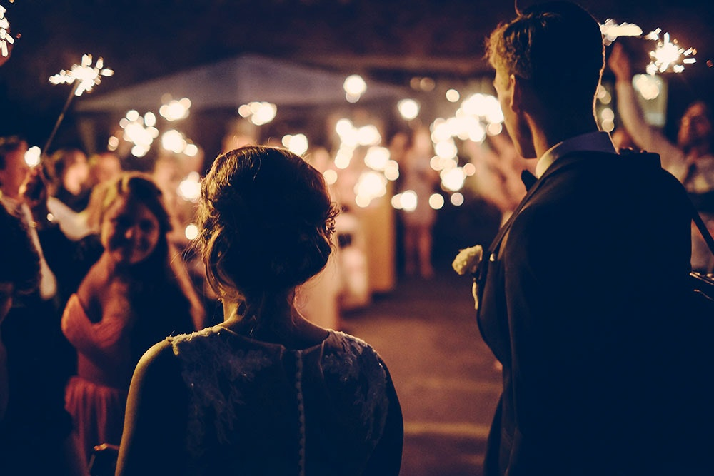 Silhouettes of a bride and groom walking towards their romantically illuminated wedding venue and a smiling guest