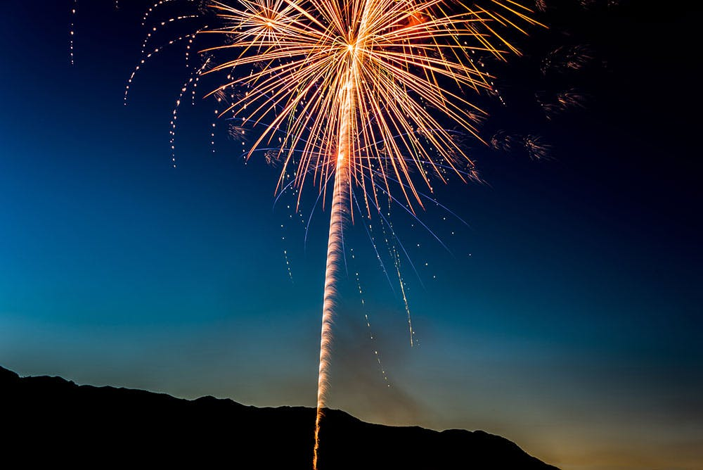 Firework illuminating a sunset sky with the silhouette of a hill behind