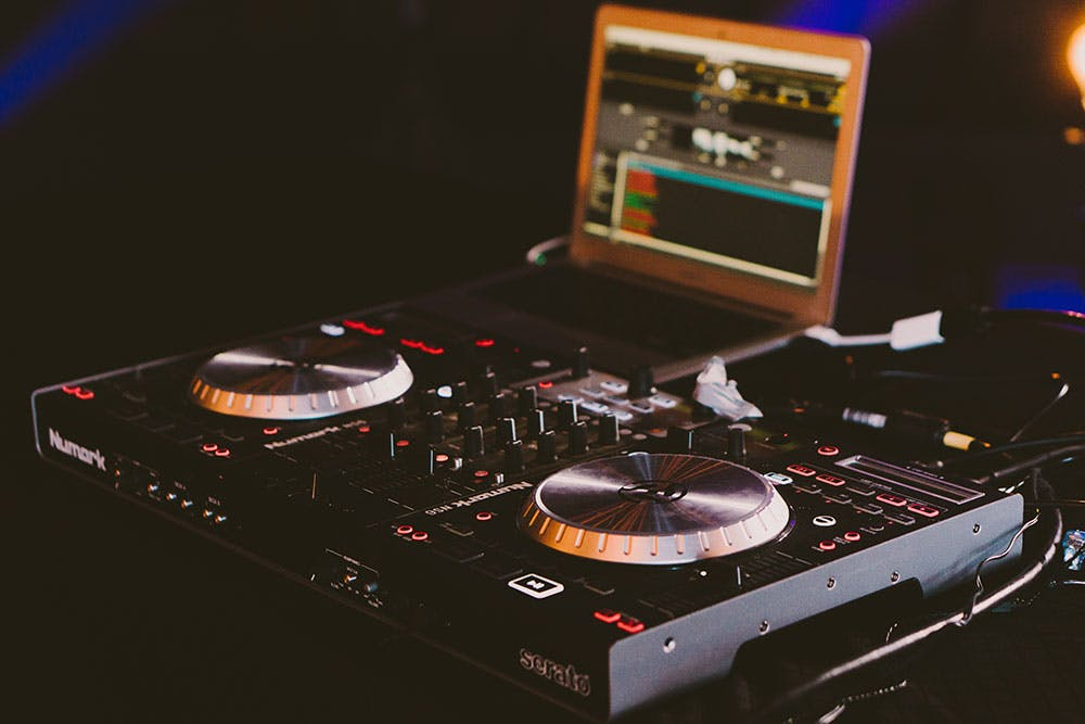 DJ turntables with illuminated buttons in a dark room and a lit up laptop in the background