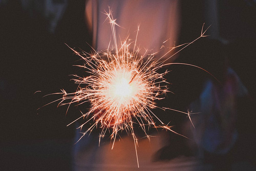 Close up of a lit sparkler candle held by a blurred out bride at night