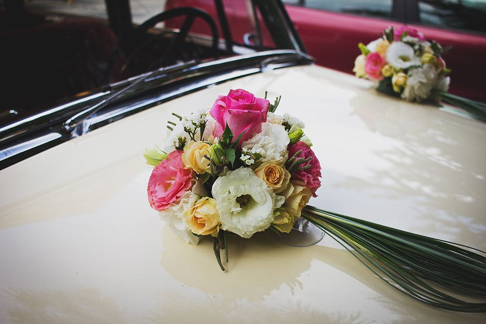 White honeymoon car bonnet with two pink, white and yellow flower bouquets