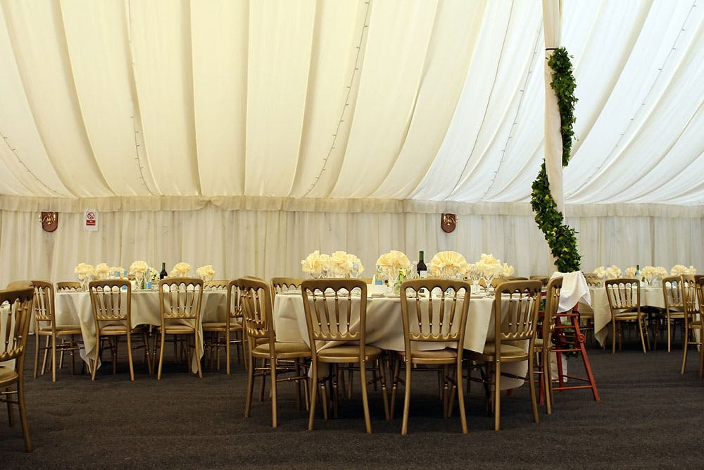 Marquee wedding venue dressed with dinner tables, fairy lights and ivy wedding decoration