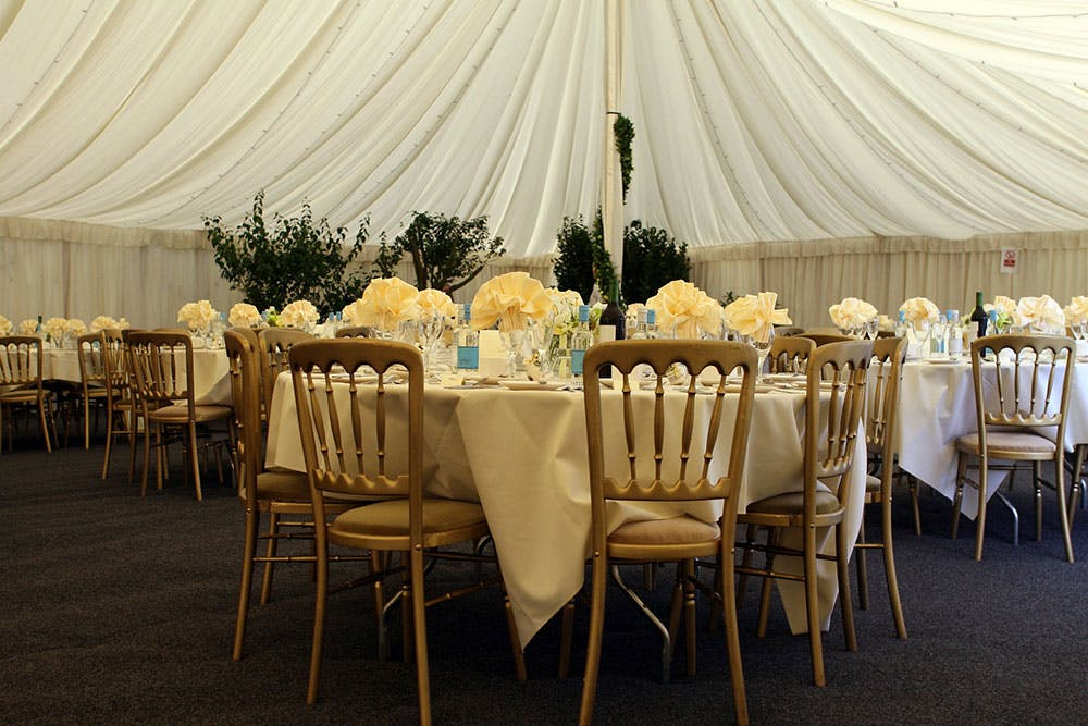 Marquee wedding venue dressed for sat down wedding breakfast, decorated with fairly lights and ivy