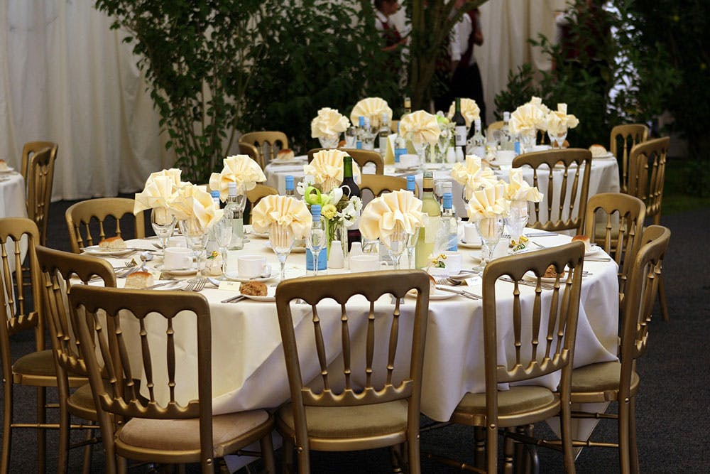 Dressed wedding breakfast table in marquee venue, with golden chairs and cream and white table cloths