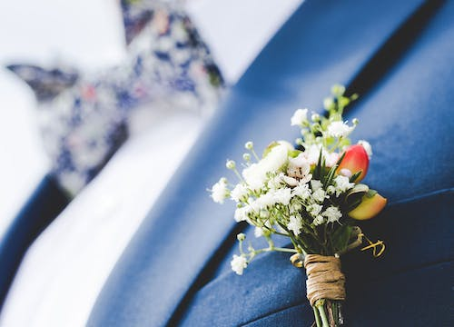 Close-up on groom wearing dark blue suit jacket with white and orange flower bouquet in pocket, and liberty bowtie