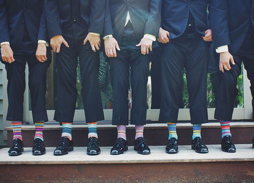 Four best men at wedding, wearing dark blue suits, pulling up trousers to reveal colourful striped socks