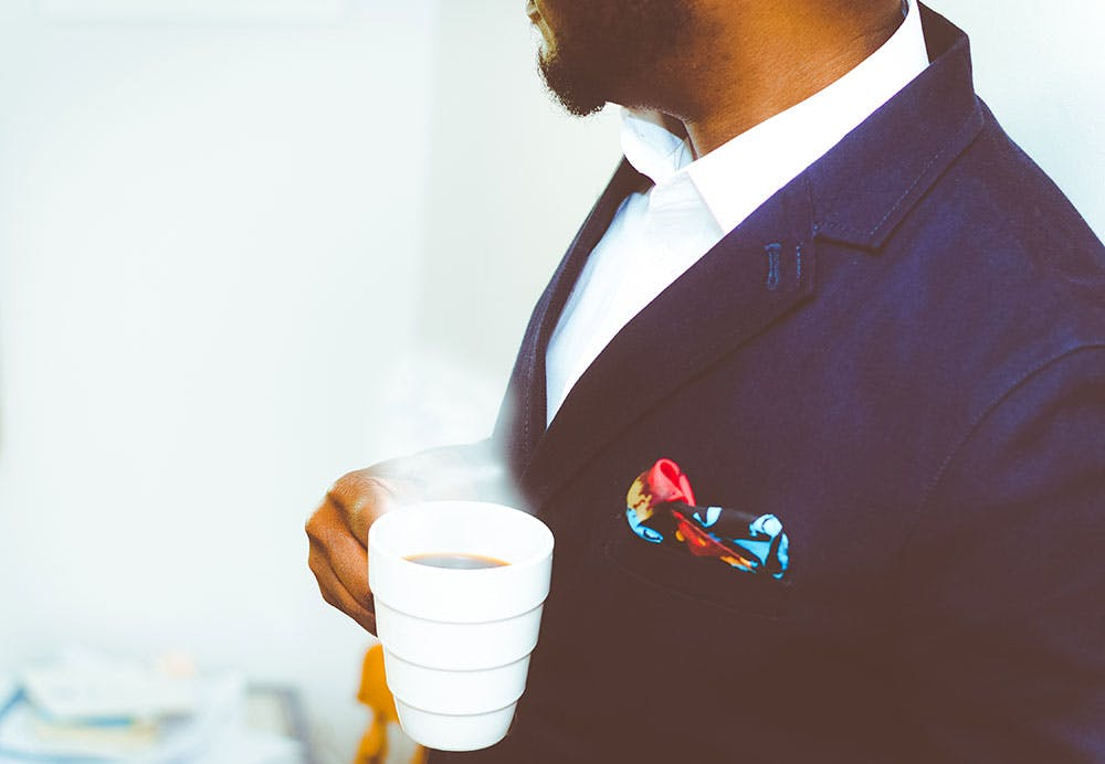 Bearded man in dark blue suit with colourful pocket square holding a cup of coffee at a wedding
