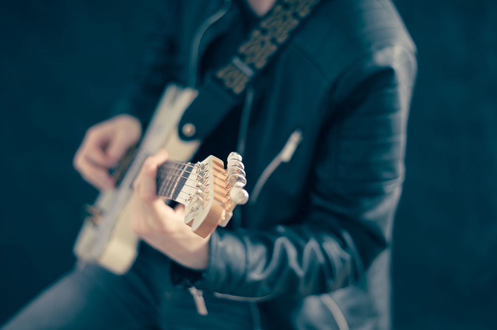 Guitarist in black leather jacket playing wooden electric guitar for a wedding band entertainment