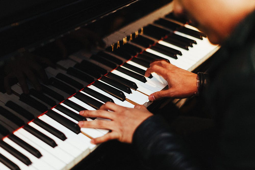 Close up on man's hand playing a Yamaha piano for live wedding band entertainment