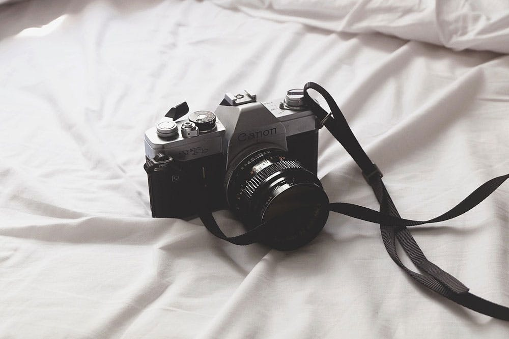 A vintage Canon FTb camera laid on white bedsheets for wedding photography