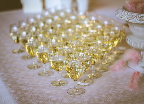 Wedding buffet table with small glasses of white wine aligned and an ornate white wooden jar filled with pink feathers