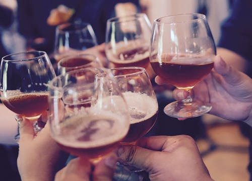 Close up of wedding guests' hands holding glasses of beer and cheering together