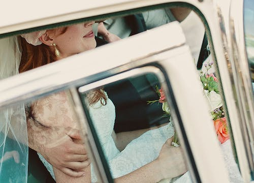 Bride sat in white car holding white and orange wedding bouquet, wearing white vintage earrings and lace wedding dress