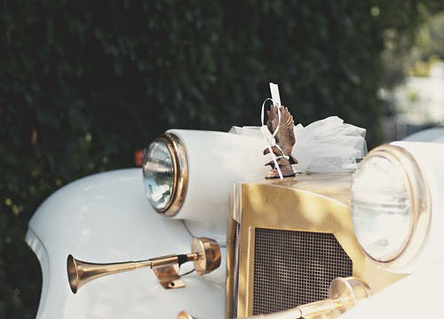 White vintage wedding car with eagle logo and vintage horn, decorated for honeymoon with white veil and ribbon