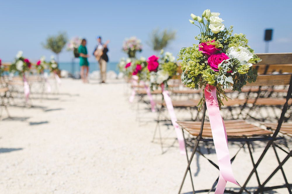 Beach wedding venue with music performers and aligned wooden chairs decorated with pink and white flower bouquets