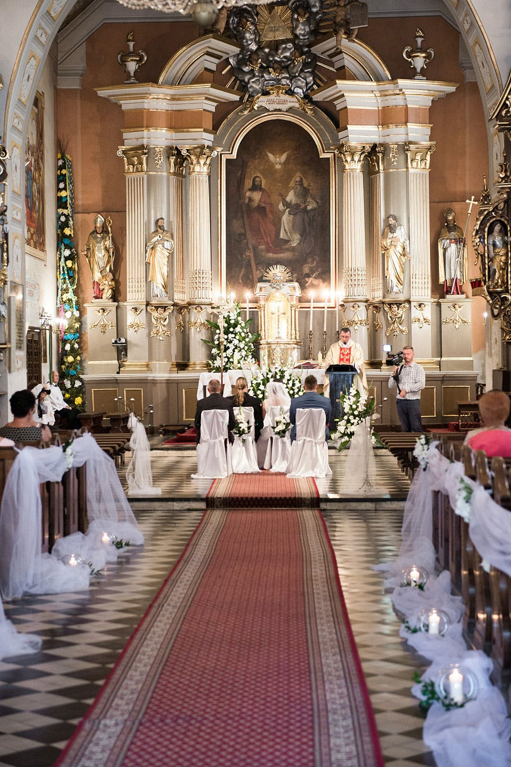 Church aisle decorated with white ribbon for wedding, guests and bride and groom sat for wedding ceremony