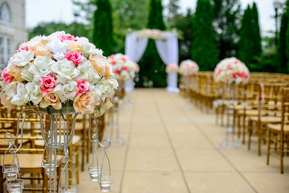 Outdoor wedding ceremony with wooden chairs set on terrace of a stately home, decorated with white, pink and orange flowers