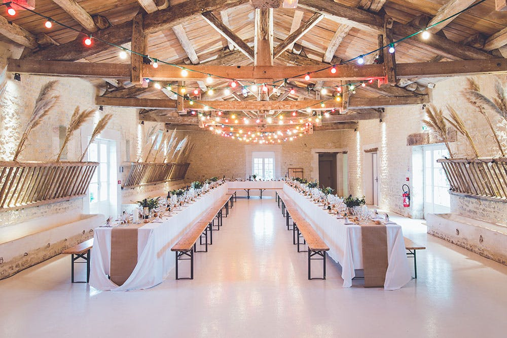 Rustic barn wedding banquet with u-shaped table, colourful fairy lights and bunches of wheat decorating walls