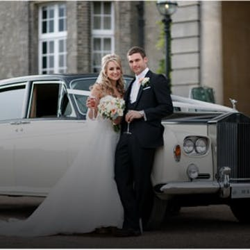 Newlywed couple standing in front of a vintage wedding car decorated with white car ribbons.