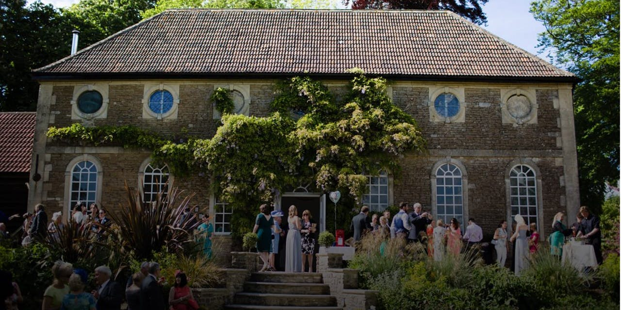 Large group of people celebrating a wedding in front of a rustic country house wedding venue.