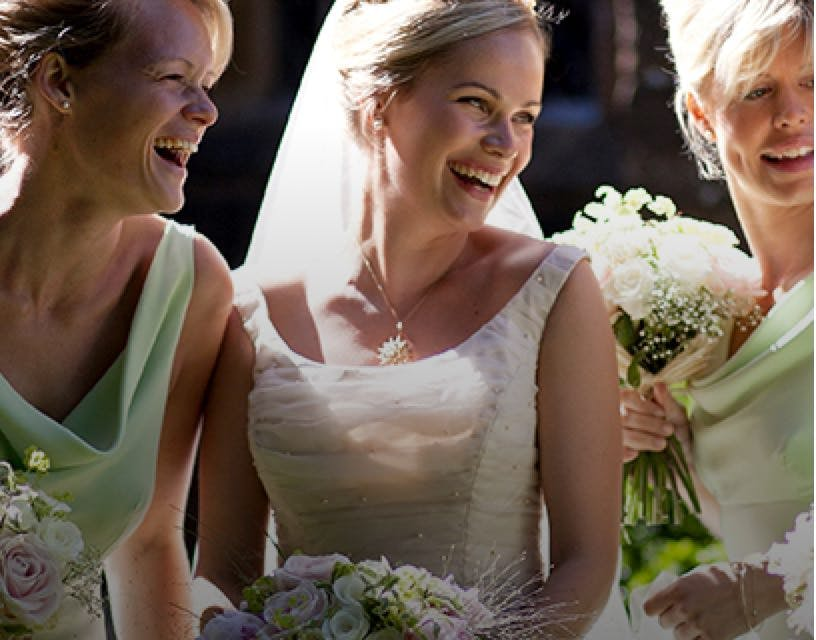 Bride wearing a boat neck white wedding dress with her two bridesmaids wearing lime bridesmaid dresses.