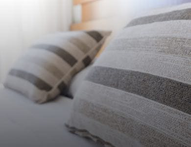 Two grey striped pillows in the double bed of a city hotel wedding venue.