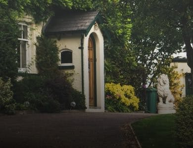 Cute country house wedding venue with a porch sticking out and a stone lion statue in front of the house.
