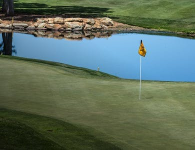 Golf course wedding venue hole 4 green with a yellow flag and a lake in the background.