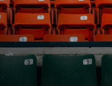 Rows of numbered black and red seats in a football stadium wedding venue.