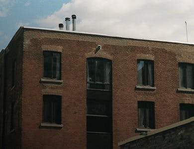Brown bricked warehouse with large windows and typical warehouse wedding venue decoration.